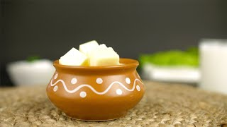 Closeup shot of a clay bowl filled with fresh butter cubes rotating on a turntable