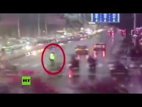 China: Un Policía Ayuda A Una Anciana A Cruzar La Calle Durante Un Aguacero