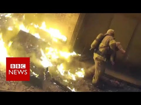 Firefighter catches child from burning building - BBC News