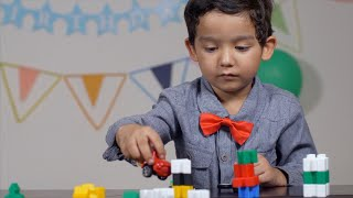 Innocent little boy playing with blocks and toy car - Having fun at home