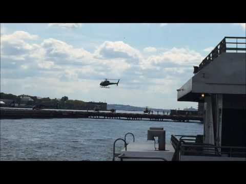 TOURIST HELICOPTERS TAKING OFF & LANDING AT THE DOWNTOWN MANHATTAN HELIPORT NEAR WALL STREET IN NYC.