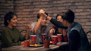 A young group of friends happily enjoying while talking and eating in a cafe