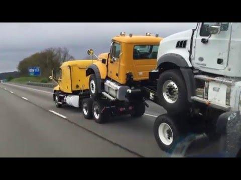 Brand new Mack trucks on the interstate - piggy back