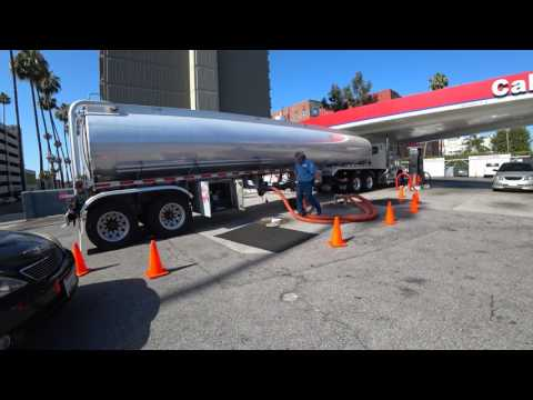 A Gas Truck Delivering Fuel At A Gas Station
