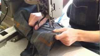 Mending pair of Nudie Jeans at Nudie shop in Gothenburg.