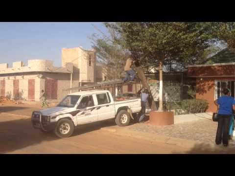 Destino SENEGAL: Hombres colocando un poste con una camioneta
