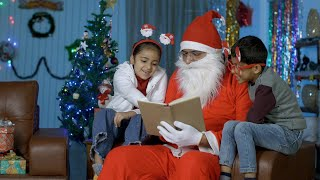 Indian kids reading a book along with Santa Claus while sitting in a decorated Christmas room