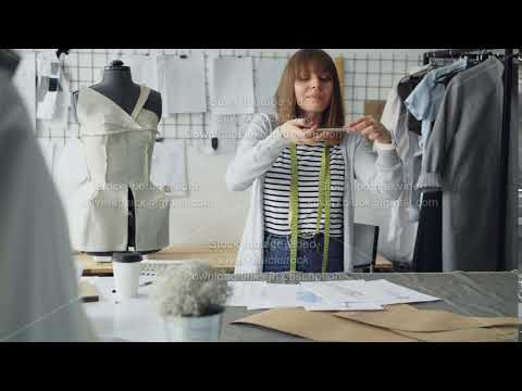 Ambitious creative female tailor is placing garment sketches on studio desk and shooting them with