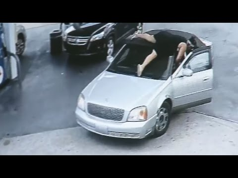 Woman leaps on thief's car at gas station