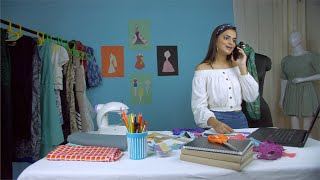 Indian fashion designer busy on a business call in her self owned fashion studio