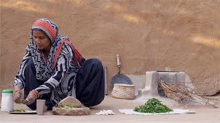 Indian rural woman adding ingredients to prepare chutney in a stone grinder