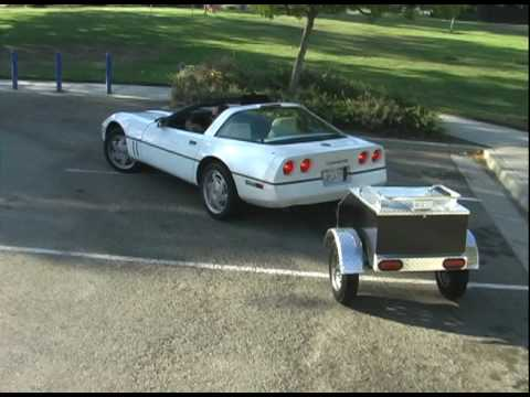 Small Car cargo luggage trailer packed up behind a Corvette