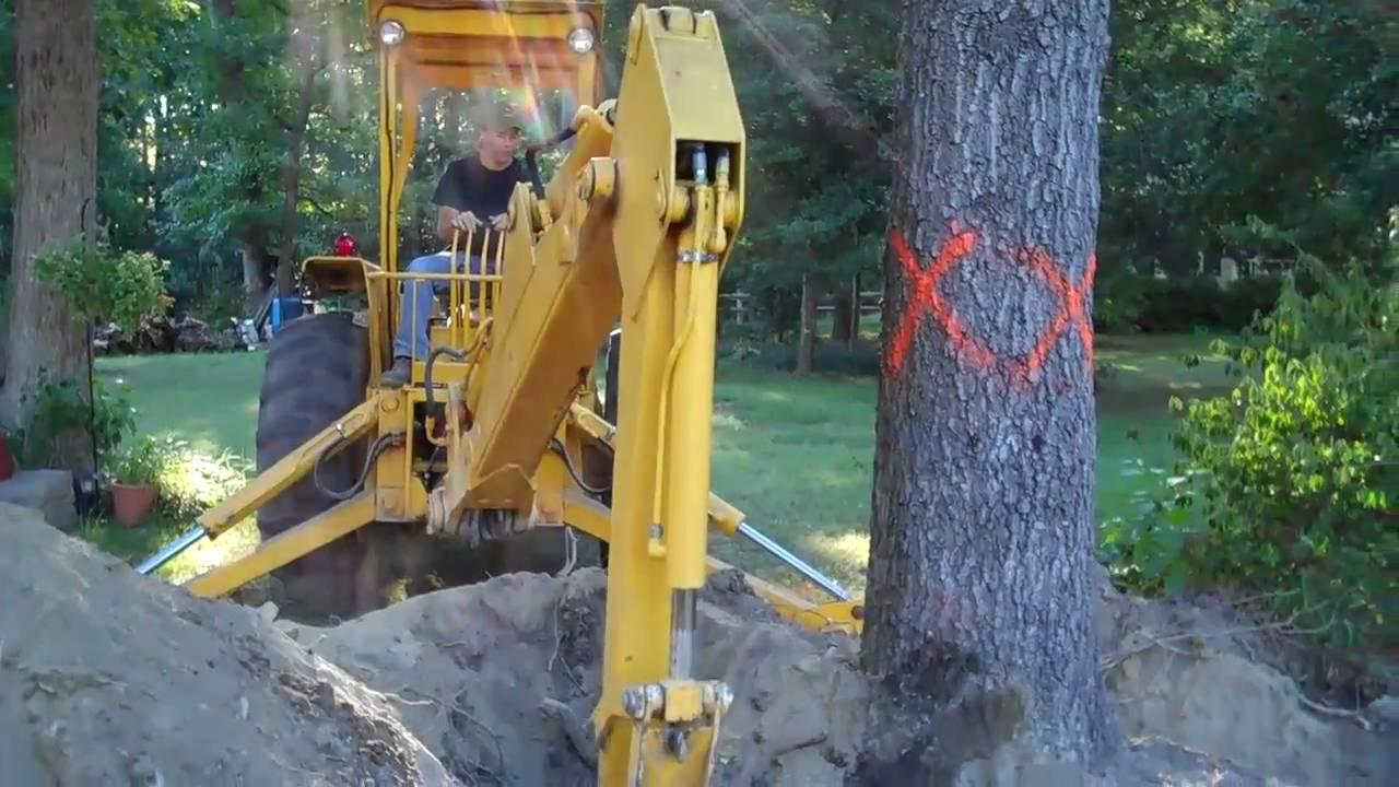 Backhoe Digging Out Stump