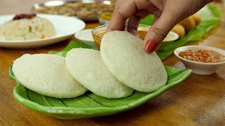 Close up of woman hands serving steamed Idli with various South Indian dishes in the background