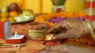 Newlywed Indian female taking traditional Indian tilak sindoor from a golden case