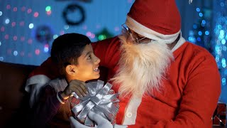 Bokeh shot of cute Indian kid opening a magical gift box with old Santa Claus