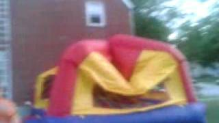 father jumps off roof- on to a kids moon bounce