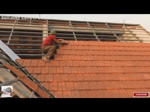 building construction installation terracotta roof tiles on a fixed frame