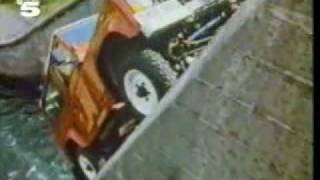 land rover defender driving 45 degrees  up an hydrodam wall