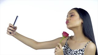 Side view of an Indian female smiling and pouting while taking selfies with a rose