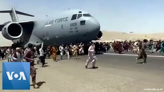 Afghans Try to Flee at Kabul Airport Crowds of people run alongside a U.S. Air Force jet at Kabul's international airport Monday, August 16., From YouTubeVideos