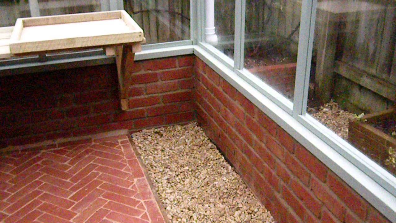 Timber greenhouse on dwarf wall with brick pathway - YouTube