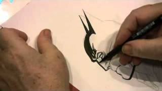Neal Adams Drawing Batman inside a copy of the Art of Neal Adams
