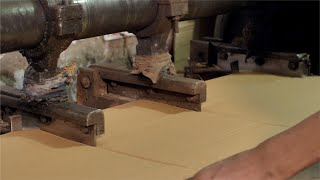 Closeup shot of a worker working on a cardboard slitting machine