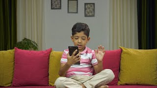 Young innocent kid busy doing a video call on his smartphone - modern technology