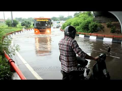 Cars splash through accumulated water at Medical flyover, Delhi