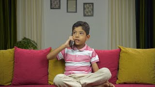 Cute little boy talking over a phone call on his smartphone - technology concept
