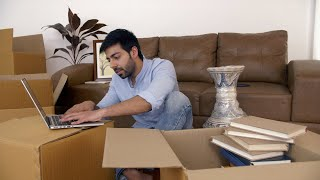 Young Indian man working on laptop amidst shifting of the new house - Relocation to metro city