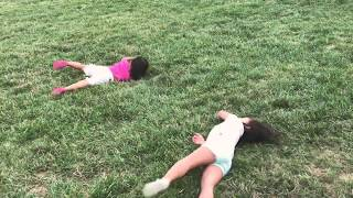 Silly kids rolling on flat grass
