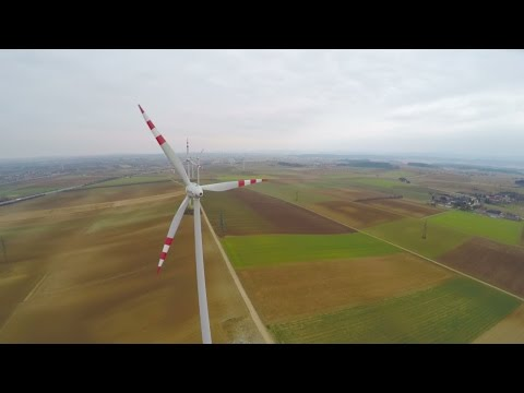 Wind turbines rotating on green field. Alternative source of energy. Aerial view. Stock Footage
