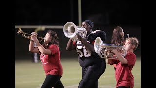 High school student puts down the football for a horn at halftime