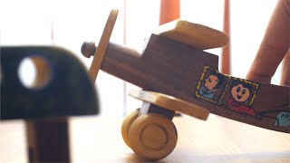 A small kid / boy is playing with a wooden toy glider and pushing it on the table
