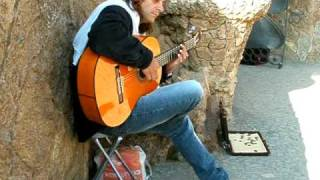 Busker playing classic Spanish guitar music in the Parc Guell, Barcelona