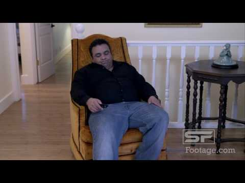 Man sitting in armchair done watching TV, stands and evaluating his weight