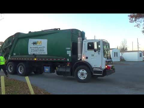 Waste Management Garbage Truck Rear Loader Is Picking Up Trash