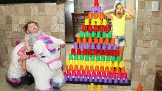 Valentina brincando com copos coloridos