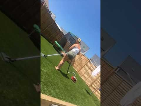 The wife dancing while cleaning the artificial grass
