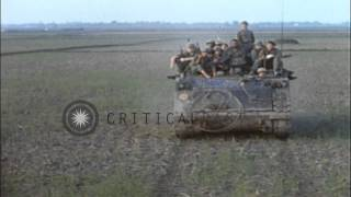 Vietnamese soldiers walk past US soldiers on a tank in Vietnam. HD Stock Footage