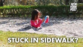 Internet baffled by photo of girl seemingly stuck in sidewalk | New York Post