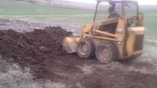 Loading the dumptruck with the skidsteer and unloading it
