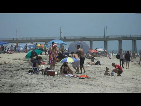 California Locals Sunbathe And Enjoy The Water At Huntington Beach On Memorial Day | AFP