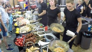 Many Woks Cooking Fish and Noodles. Kiev Street Food, Ukraine