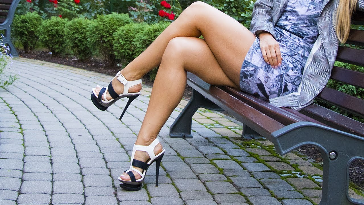 Girl on high heels sits on a bench
