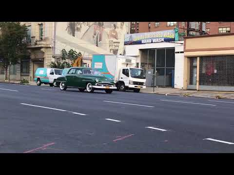 VERY OLD 1951 OR 52 PLYMOUTH CRUISING DOWN 3RD AVENUE IN MOTT HAVEN AREA OF THE BRONX, NYC.