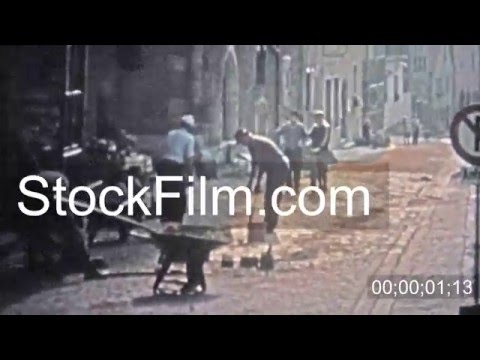 1966: Man repairing cobblestone road with old country techniques. HAMBURG, GERMANY