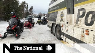 Tourists missing, guide dead after snowmobiles go through ice in Quebec